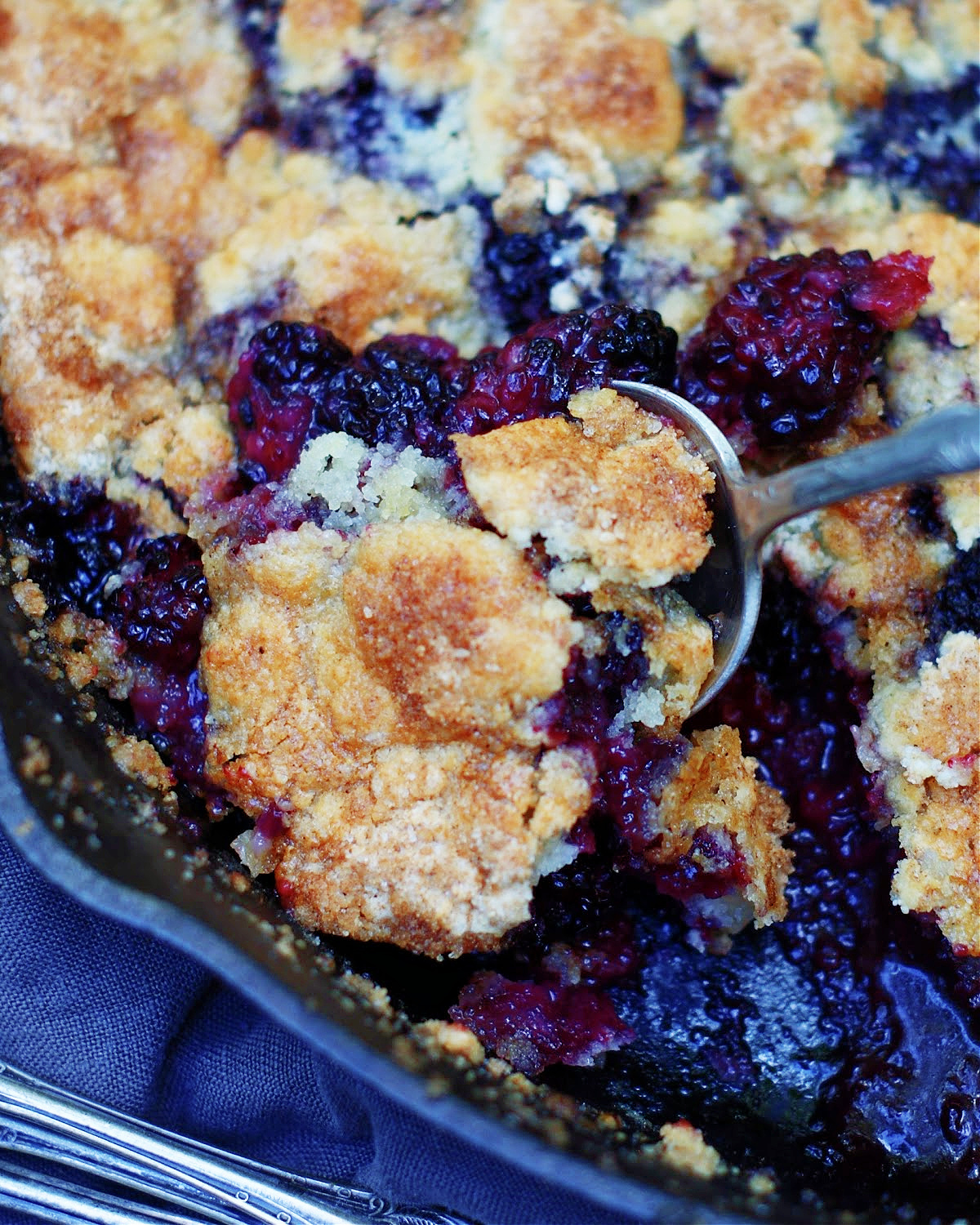 Serving Easy blackberry cobbler from the skillet to show simple crust and berries.
