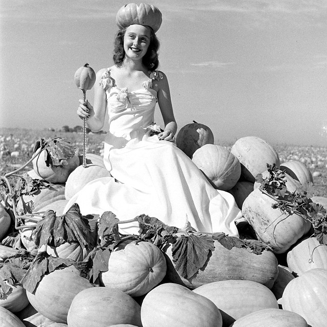 A county fair queen sitting on a pile of pumpkins and wearing a pumpkin crown.
