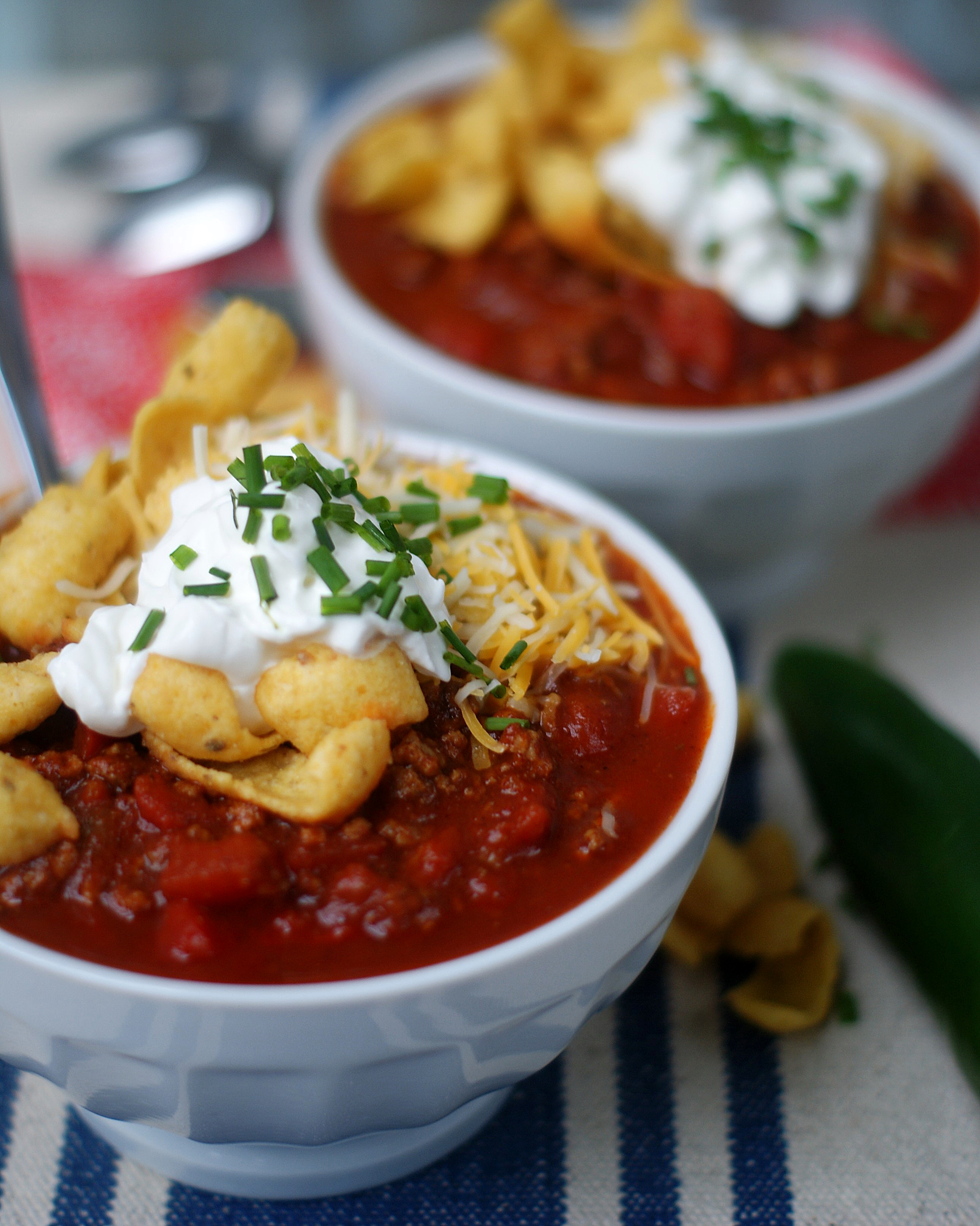 2 bowls of Texas Chili with corn chips, sour cream and cheese.