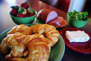 7 large golden croissants pictured on a green plate. In the background, strawberries are piled in green bowl, a sliced ham, spinach and cream cheese are on a red plate.