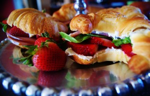 Two croissants stuffed with strawberries, spinach, and ham and garnished with extra strawberries and served on a beaded sliver platter.