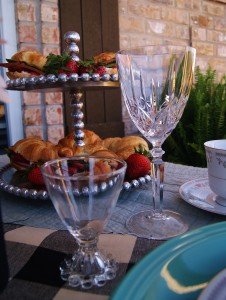 An Easter picnic table shot with strawberry cream cheese sandwiches in the background on a 2 tiered beaded silver serving tray.