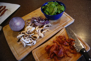 Chopped bacon, red onions, mushrooms, and leaf spinach for a spinach salad on a cutting board with a knife.