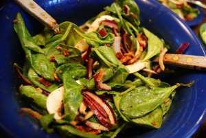 Spinach salad tossed with hot bacon dressing in a large blue bowl.