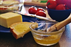 Melted butter in a small dish with a brush. Butter and butter bread and tomatoes are in the background.