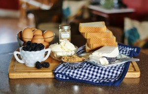 Ingredients for the blackberry grilled cheese are pictured- brown eggs, blackberries, Texas toast, butter, brown sugar, and fontina cheese.
