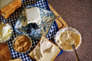 Ingredients of the blackberry grilled cheese on a cutting board with a blue and white gingham napkin.