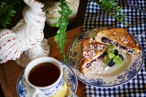 Halves of a blackberry grilled cheese stacked on a blue and white plate pictured with a white rooster, a cup of tea with lemon, and a blue and white gingham napkin.
