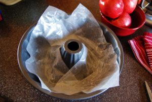 a bundt pan lined with wax paper for baking a fresh apple cake.