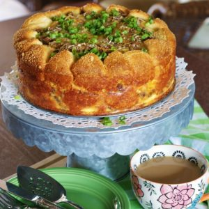 Sausage, egg and cheese brunch cake garnished with green onions and displayed on a galvanized metal cake stand with a paper doilie. Green dessert plates and a cup of coffee are pictured in the foreground.