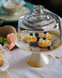 Upclose of woodland Easter tablescape pedestal dish holding3 lemon tarts with blueberries.