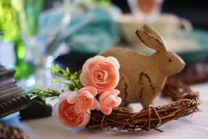 Woodland Easter tablescape bunny in grapevine wreath with 4 pink rosettes.
