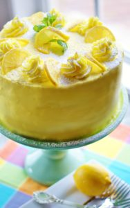 Lemon layer cake iced with yellow buttercream on a turquoise cake pedestal and pastel checked napkin.