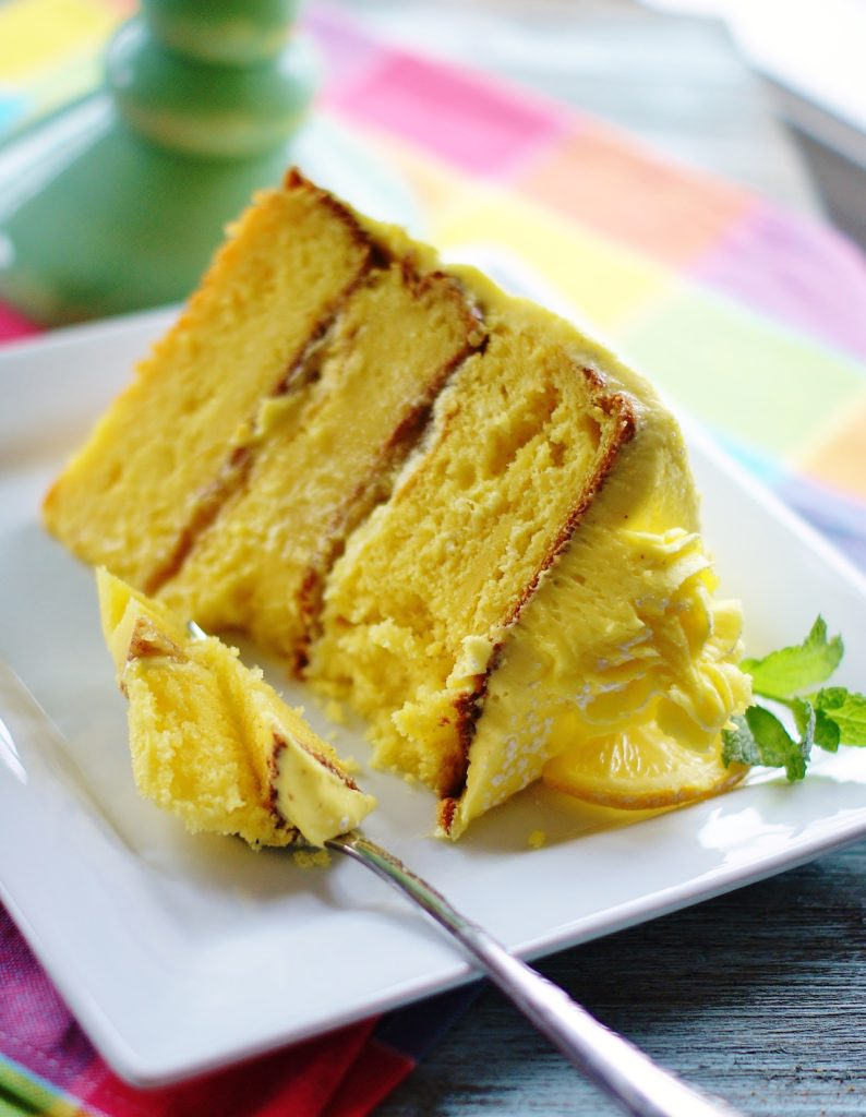 A large slice of lemon cake on a white plate.