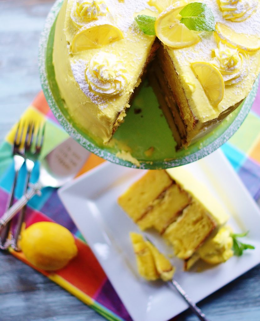Close up of the top of the lemon cake with a triangular slice missing. A slice of cake is in the background.
