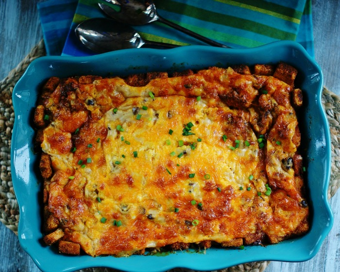 An aerial dish of a baked overnight sausage breakfast casserole with croutons in a blue baking dish.