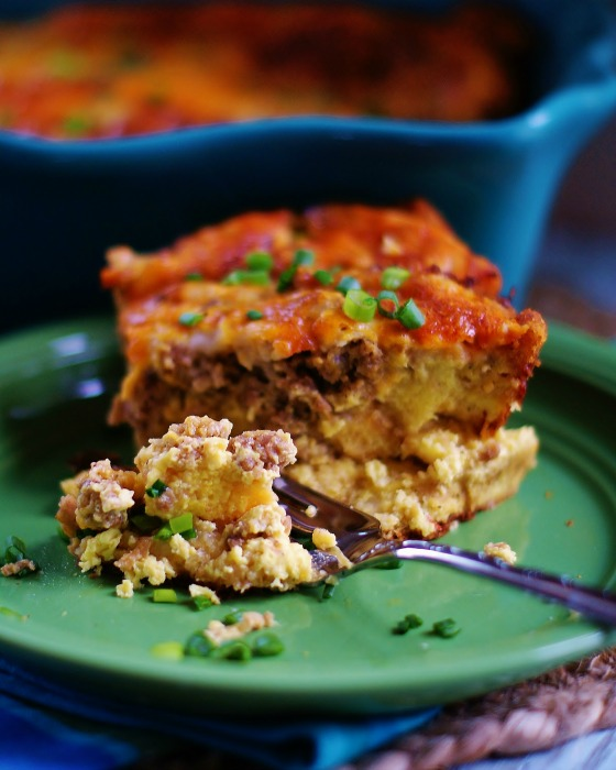 Uplose of a slice of breakfast casserole full of sausage, eggs, cheese, and bread on a green plate.