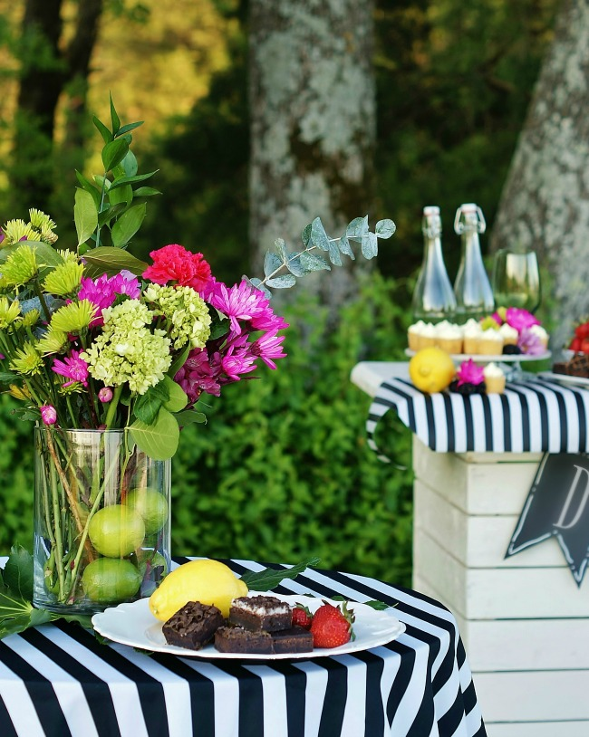 Bright spring flowers in lime green and hot pink are gathered in a vase with limes atop a pub table with a black and white striped tablecloth.