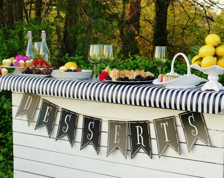 A white wooden bar, topped with a black and white striped table runner, a chalkboard pennant banner that spells out desserts and laden with colorful spring desserts and fruit.