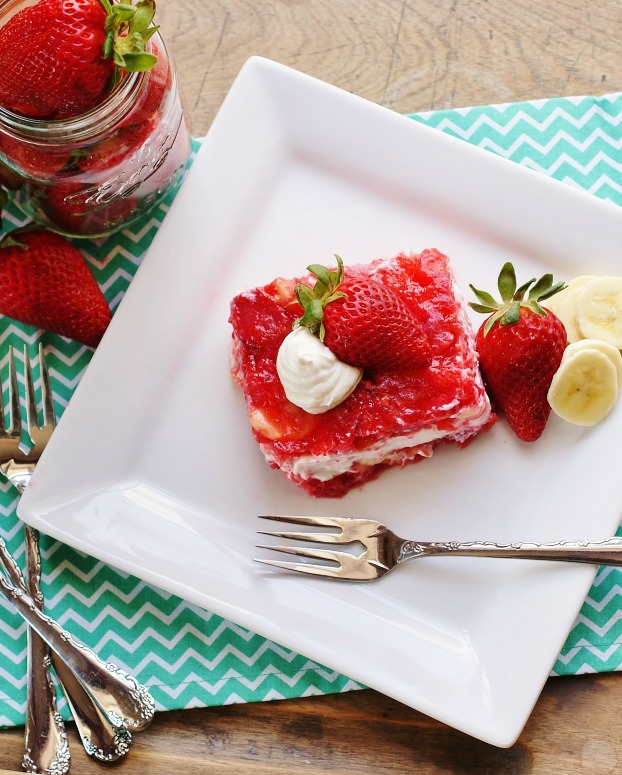An aerial view of a square of strawberry congealed salad topped with a strawberry and a dollop of sour cream. A strawberry and banana slices are also on the plate, all sitting on a turquoise napkin.