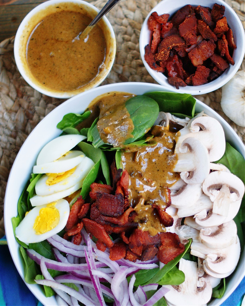 Drizzling Hot Bacon Dressing over Spinach Salad with mushrooms, red onion and boiled egg