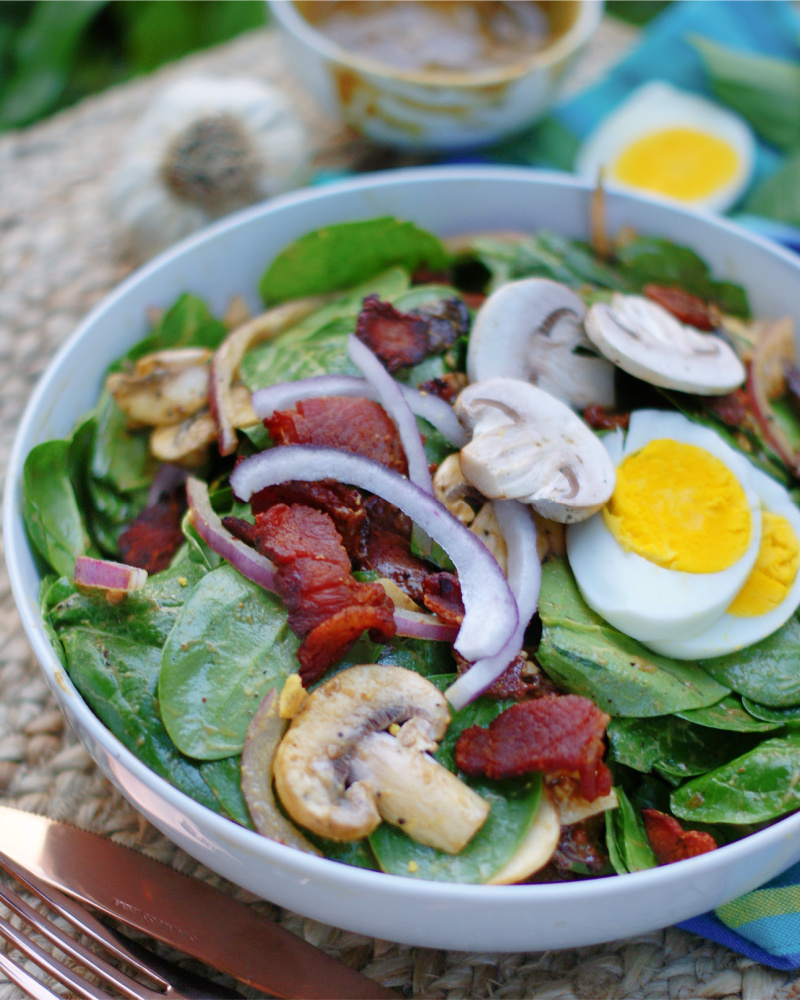 Serving Hot Bacon Dressing and Spinach Salad in a bowl.