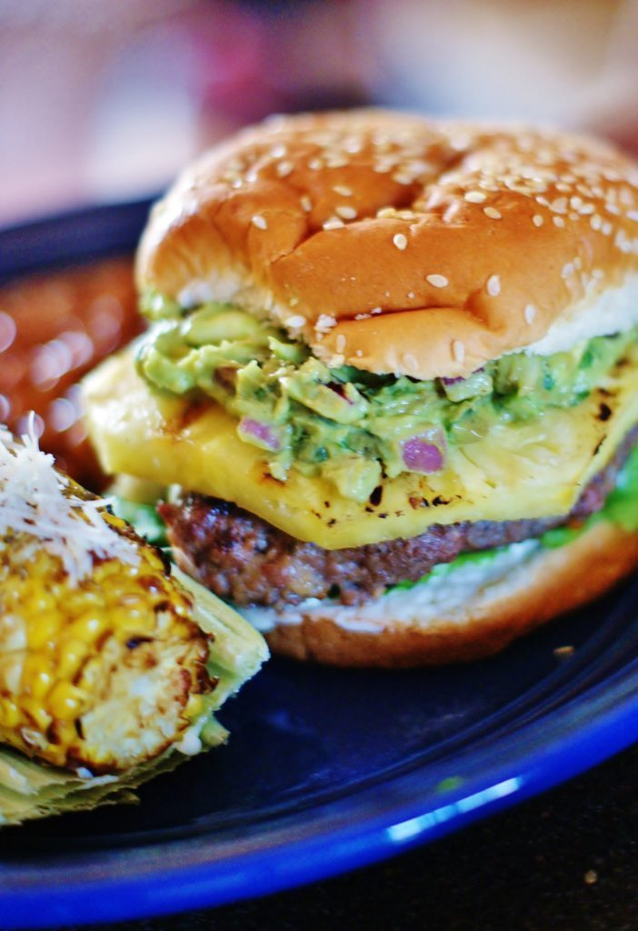 Grilled beef and ground sausage burger with grilled pineapple slice and avocado spread. The perfect cookout recipe for this weekend.