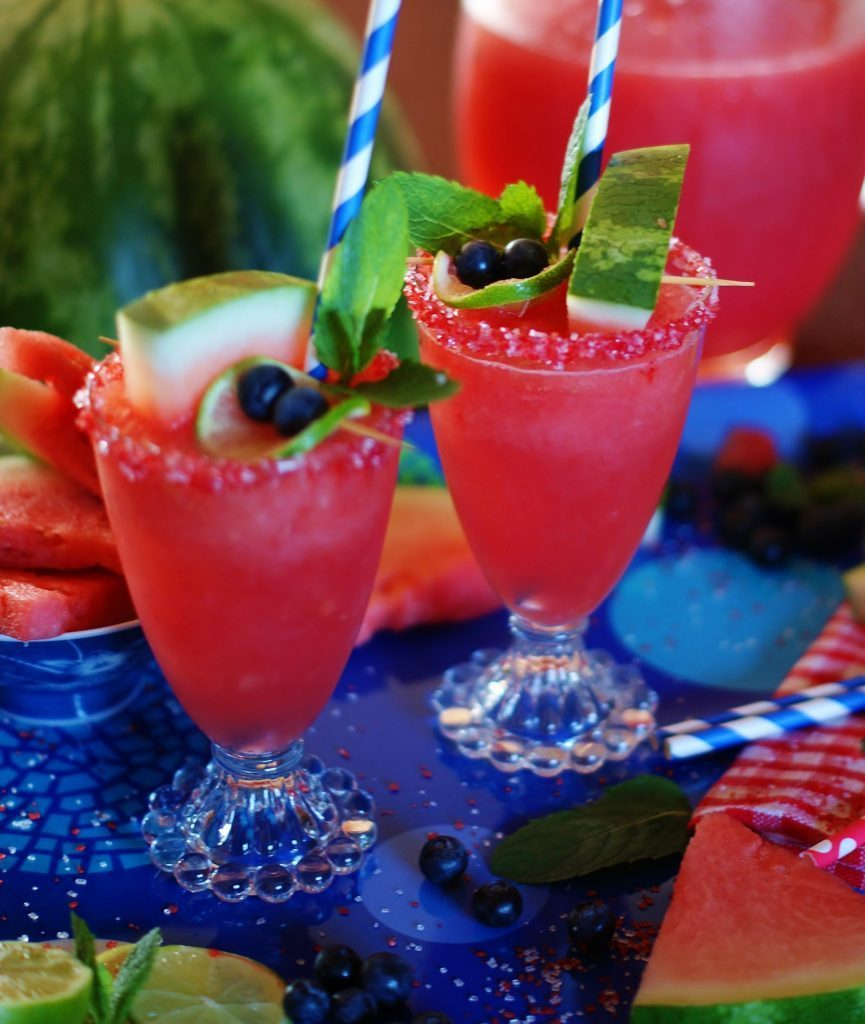 Fresh watermelon, lime, and a little bit of fizzy make this summer sipper a great cookout recipe. Watermelon sparklers garnished with watermelon wedges, mint leaves, and blue and white straws.