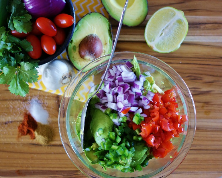 A clear glass mixing bowl full of avocado, diced red onions, diced grape tomatoes, and diced jalapeno. Half an avocado, limes and spices are in the background with a yellow and white chevron napkin.