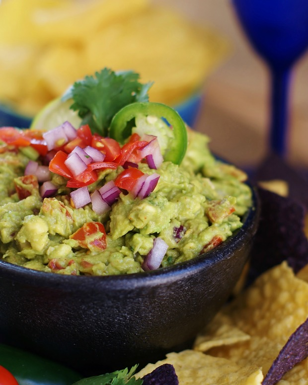 Upclose of fresh Tex Mex guacamole topped with tomatoes, red onion, pepper slice, all in a black mortar.