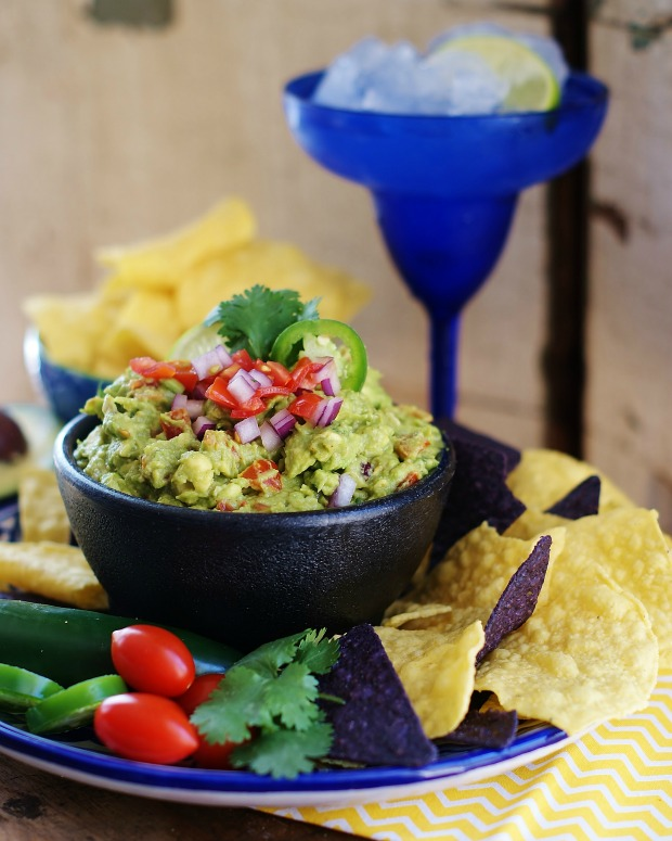 Fresh Gucamole piled hig in a mortar bowl and topped with diced tomatoes, red onions, cilantro leaf, and a jalapeno slice. Chips and a blue maragarita style glass are included.