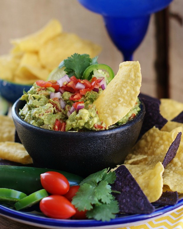 An upclose of guacamole piled high in a black mortar bowl. Yellow and blue corn chips with extra tomatoes and jalapeno peppers are in the foreground.