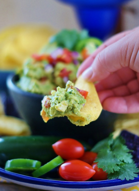 A close up of a yellow corn chip with a generous scoop of dipped fresh, homemade Tex Mex guacamole.