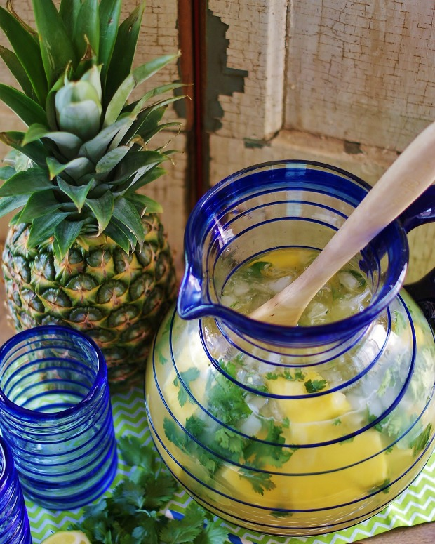 An aerial view of the pineapple limeade with cilantro in the blue-spiral-lined Mexican glass pitcher with a wooden spoon, pineapple, and spiral-lined tumbler in the foreground.