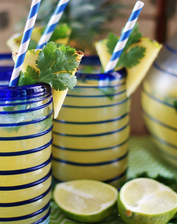 Upclose of Sparkling Pineapple Limeade with pineapple wedge granishes, blue party straws and lime halves