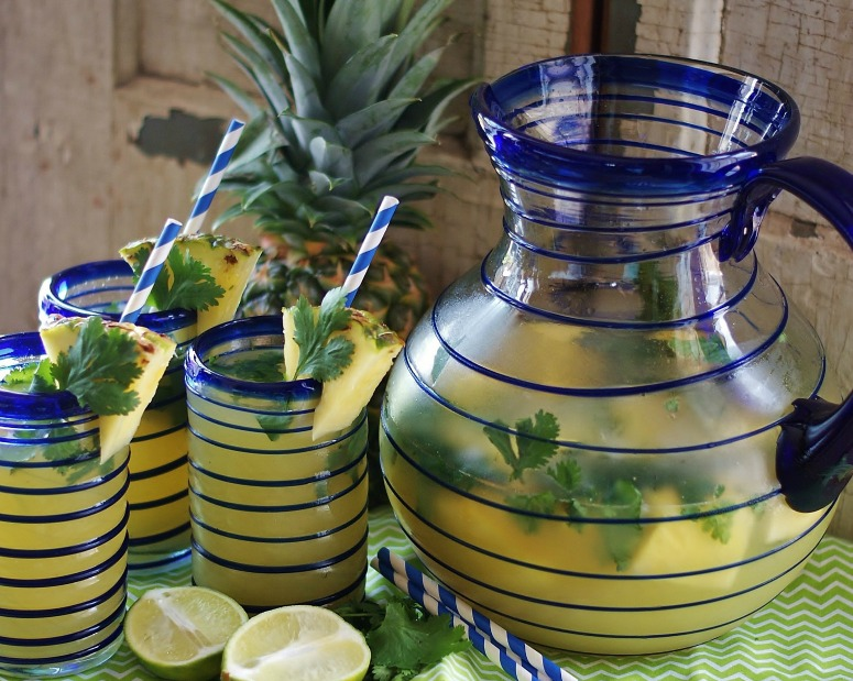 A wide-angle view of blue spiral-lined Mexican glass pitcher & three tumblers all filled with Pineapple Cilantro Lime Spritzer.