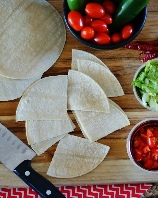 White corn tortillas cut into quarters on a cutting board.