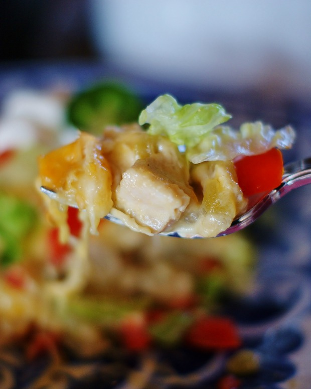 Green Chile Enchilada Casserole on a fork with tomatoes and lettuce.