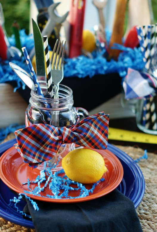 orange and blue plaid bowtie around a mason jar on a blue and orange place setting for a party.
