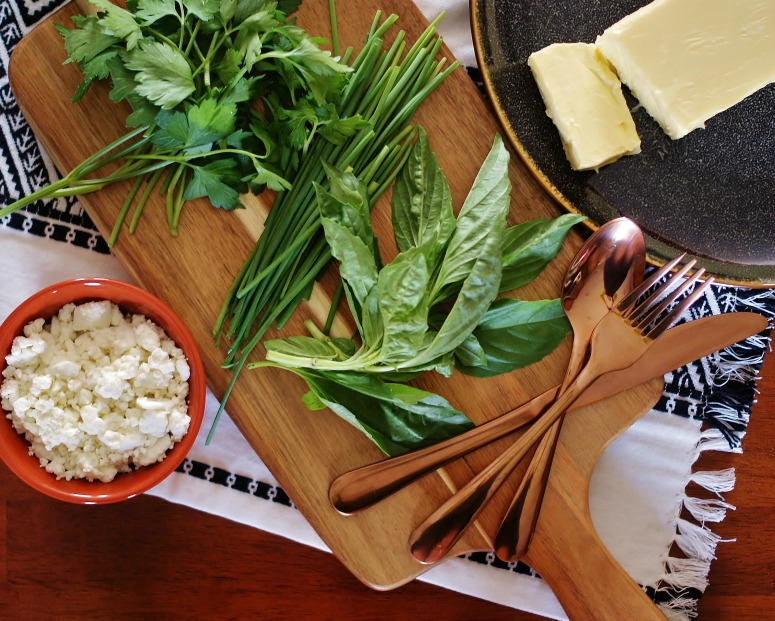 The ingredients for herbed steak butter with goat cheese & bacon on a cutting board with a black and white linen and copper utentsils.