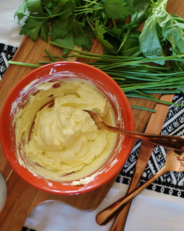 Step 1 for herbed steak butter: Butter and goat cheese mixed in an orange bowl with herbs and copper utnesils out to the side.