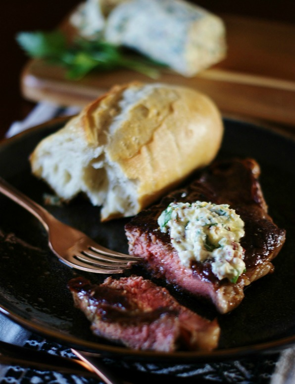 Herbed steak butter on a sliced New York strip with sour dough bread and a copper fork.