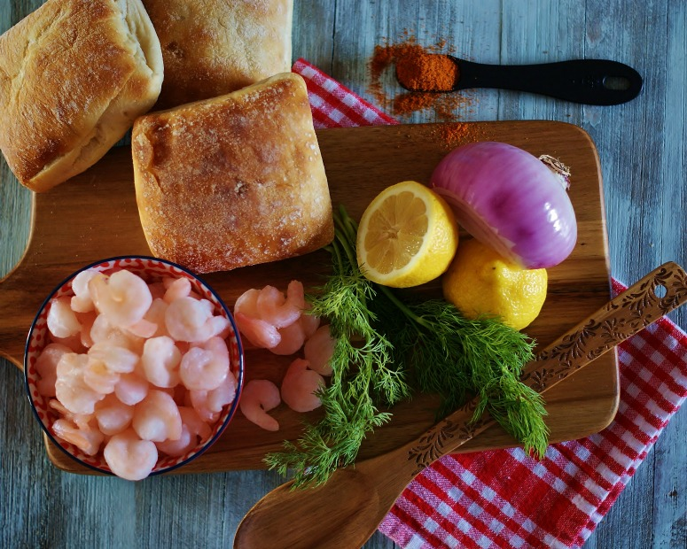 Small shrimp, dill, lemon, red onion, rolls, and seasonings gathered to make a Southern Shrimp Salad Roll.
