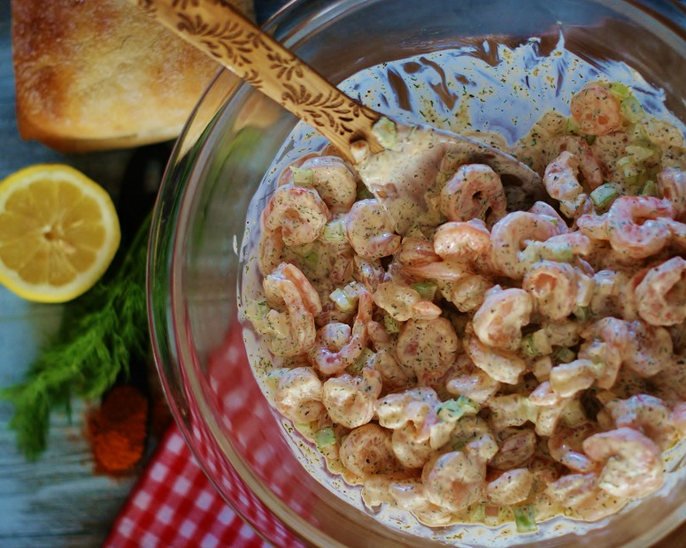 A bowl of finished shrimp salad with lemon and dill ready to be put on a roll and served.