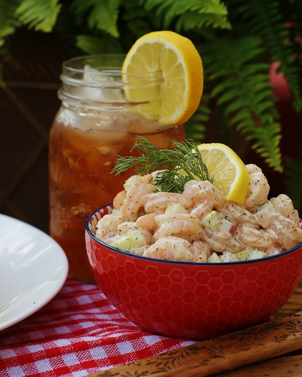 Southern Shrimp Salad with lemon and dill in a red bowl with iced tea in a mason jar garnished with lemon is in the background.