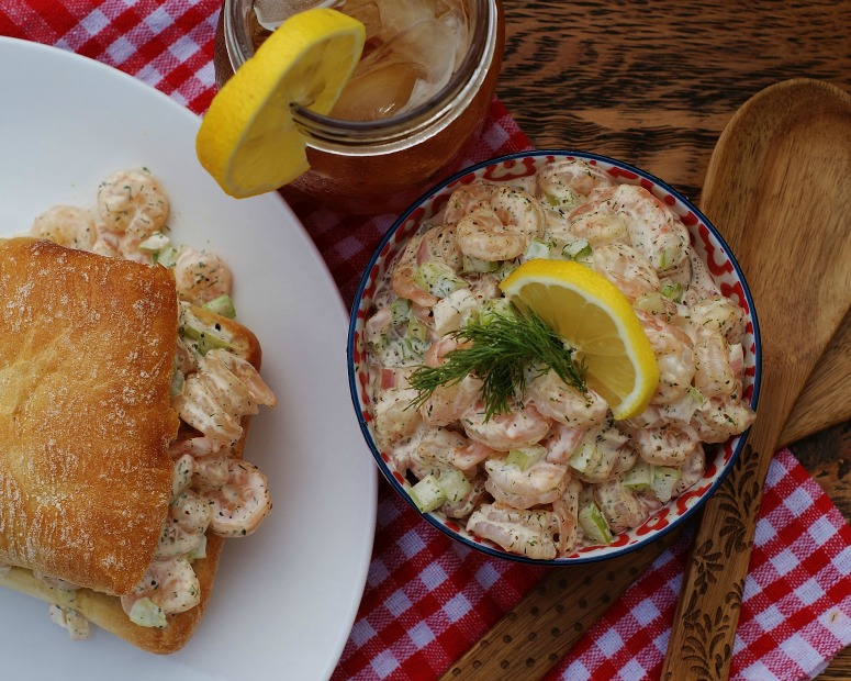 An overhead view of a bowl of Southern Shrimp Salad, iced tea in a mason jar, and a southern shrimp roll at a picnic.