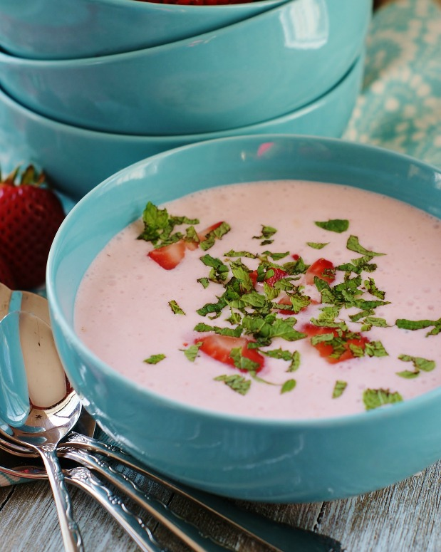 Chilled strawberry bisque in turquoise soup bowls garnished with sliced strawberries and mint.