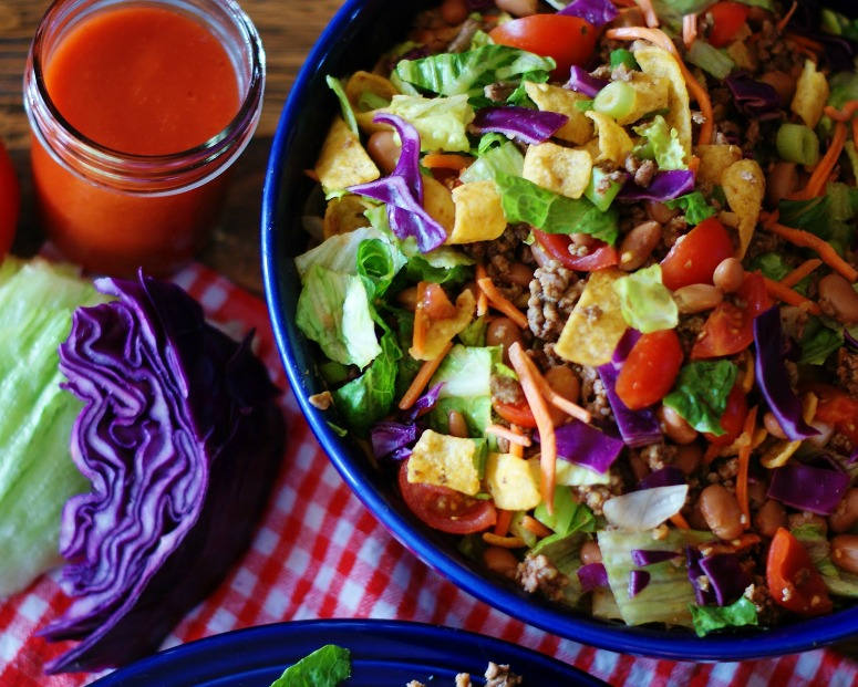 Catalina Frito Salad in a blue bowl with Catalina dressing in a jar to the side.
