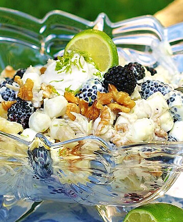 Easy summer ambrosia with a tropical flair. Filled with coconut, pineapple, blackberries and lime all swathed in clouds of cool whip, lime yogurt and mini marshmallows.