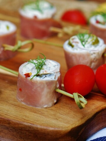 Ham & Dill Pickle Pinwheels Rollups on a wooden cutting board with cherry tomatoes.